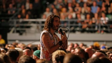 British comedian, writer and activist Russell Brand joins the crowd at Rod Laver Arena on the first date of his Trew World Order Australian tour.