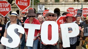 Adani protestors are seen protesting outside of Queensland's Parliament House in Brisbane.
