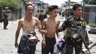 Two men who claim to be hostages are escorted to a waiting vehicle after being released from the hands of Muslim rebels in Zamboanga city in southern Philippines on September 17, 2013.