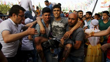 An injured man is carried away after the  explosion at an election rally in Diyarbakir.