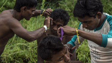 Rescued Rohingya men from Myanmar have haircuts at the confinement area in Kuala Langsa.
