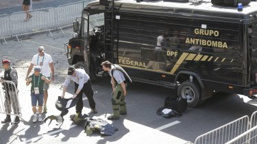 Members of Brazilian bomb squad pack their gear after detonating a suspicious package near the men's cycling road race final in Copacabana.
