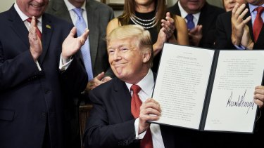 US President Donald Trump holds up a signed executive order on health care designed to expand health insurance options for some Americans, in a move that may also undermine coverage for those who remain in Obamacare.