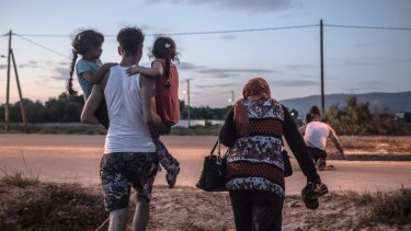 A Syrian refugee from Deir Ezzor carries his siblings ashore after arriving on the island of Kos in Greece.