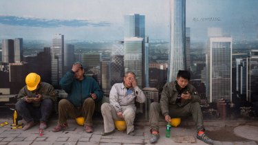 Construction workers rest near a board with an artist's impression of the Central Business District outside a construction site in Beijing.