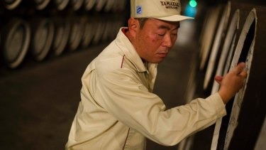 Senior general manager of the Yamazaki Distillery, Takahisa Fujii, knocks on whisky casks to check levels in the distillery's storage.