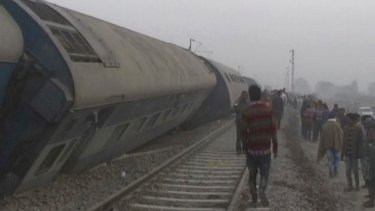 People gather at the site of a train accident near Pukhrayan, about 270 kilometers from Allahabad, Sunday.