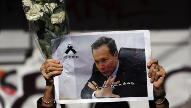 A woman holds up flowers and an image of late prosecutor Alberto Nisman.