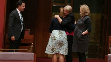 Greens senators Sarah Hanson-Young, Janet Rice and Larissa Waters embrace after the vote.