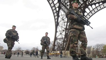 French army soldiers patrol under the Eiffel Tower.
