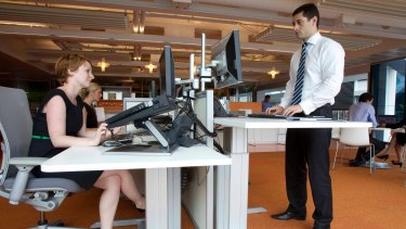 Employees using both sitting and standing desks at the Macquarie Group headquarters in Shelly Street, Sydney.