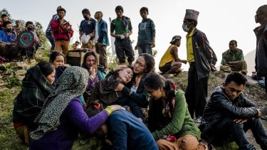 A mother is consoled on Tuesday after the funeral of her son, whose body was discovered under the rubble of houses destroyed during a massive earthquake in Nepal.