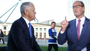 Former member for Hindmarsh Matt Williams walks past while Prime Minister Malcolm Turnbull is interviewed by David Koch following the 2016 budget.
