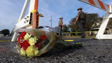 A bouquet of flowers lies at the base of a roadblock where law enforcement officials work at the scene of the shooting
