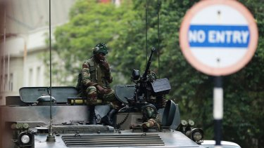 Soldiers sit on a military vehicle parked on a street in Harare, Zimbabwe, on Thursday.