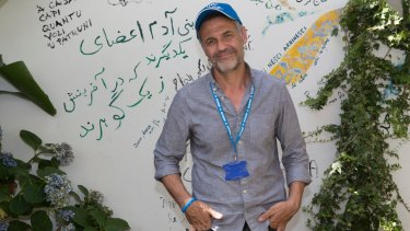 UNHCR goodwill Ambassador Khaled Hosseini beside a  poem he wrote on the walls of of the refugee-run Orient Experience restaurant in Sicily.
