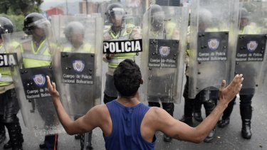 A protester gestures in front of police during an opposition march in Caracas on May 11.