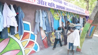 Children help themselves to donated items at the Wall of Kindness in Bhilwara, India.