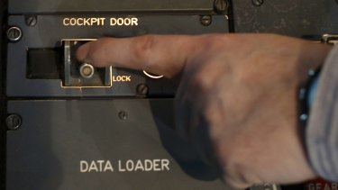 Sealed in: A person moves the switch of the cockpit door locking system inside a flight simulator of an Airbus A320 in Vienna.