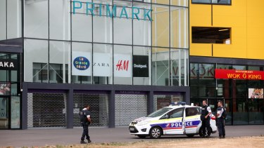 Police officers stand outside the Primark clothing store, in Villeneuve-la-Garenne, north of Paris, on Monday. Up to 10 employees were trapped inside with as many as three gunmen, police said.