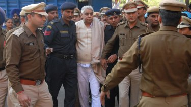 Indian guru Rampal Maharaj  is escorted by Haryana police out of the police vehicle on his arrival at the Punjab and Haryana High Court