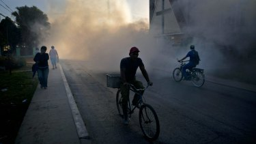 People make their way through pest-control fog, sprayed to kill Aedes Aegypti mosquitos in Cuba in March.