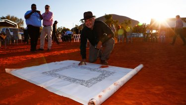 Noel Pearson signs the canvas last week on which the Uluru statement will be painted.
