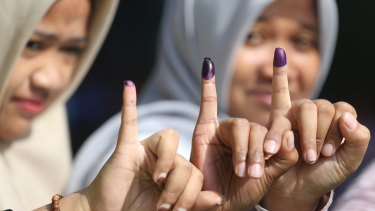 Women show their ink-stained fingers after voting during the runoff election in Jakarta.