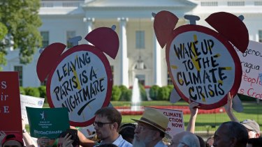 Climate protesters gather outside the White House against Trump's decision.