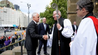 Melbourne Archbishop Dr Philip Freier greets Prime Minister Malcolm Turnbull outside St Paul's before the funeral.