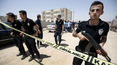 Security guards cordon off a building after two police officers were found shot dead in Ceylanpinar.