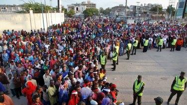 Protesters gather near the scene of Saturday's massive truck bomb attack, near the presidential palace, in Mogadishu.