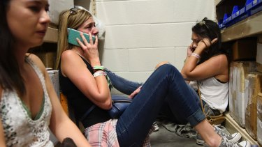 Women make phone calls while taking shelter inside the Sands Corporation plane hangar during the Las Vegas shooting.