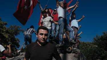 Protesters climb a damaged  tank in Ankara after the failed July 2016 coup.