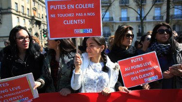 """Sex workers hold signs reading """"Prostitutes are angry. Don't touch our customers"""" during a protest before the new bill against prostitution and sex trafficking passed in Paris on Wednesday."""