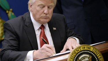 President Donald Trump signs an executive order in Washington.