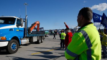 Hutchison Ports Australia workers stop a truck entering at Port Botany, Sydney, after being sacked by email overnight.