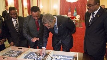 "Ethiopian Prime Minister Hailemariam Desalegn watches as President Barack Obama touches ""Lucy,"" part of several hundred pieces of bone representing 40 percent of a female Australopithecus afarensis who was estimated to have lived 3.2 million years ago in Ethiopia."