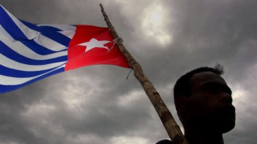 A Papuan holds the Morning Star independence flag, an act for which dissident Filep Karma was jailed for 15 years.