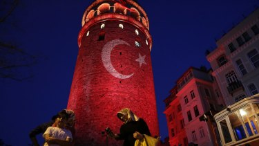People take photos with their phones at the iconic Galata Tower, illuminated in Turkish flag colours, in Istanbul on Saturday.