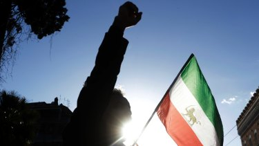 A demonstrator holds the flag of monarchy-era Iran outside the Iranian embassy in Rome.
