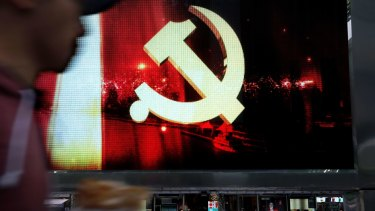 A man walks by display showing the Communist Party logo in Shanghai this week.