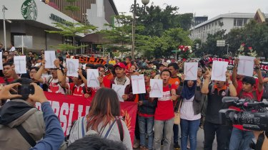 """Jakarta football club supporters sing while holding letters saying """"kami tidak takut"""" ('We are not afraid') at an anti-terrorism rally outside Starbucks where a suicide bomb was detonated."""