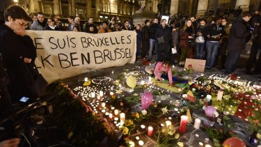 """A banner reading """"I am Brussels"""" behind flowers and candles to mourn for the victims at Place de la Bourse in the centre of Brussels."""