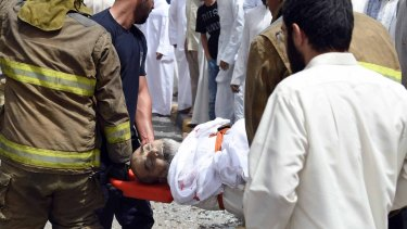 A wounded man is helped moments after a deadly explosion claimed by the Islamic State group during Friday prayers at the Imam Sadiq Mosque in Kuwait City.