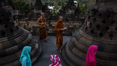Buddhist monks and sightseers  at Borobudur temple  in Central Java.
