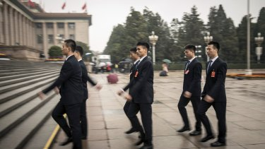 Security personnel walk towards the Great Hall of the People after the opening of the Communist Party Congress this week.
