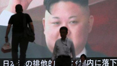 People walk past a TV screen showing an image of North Korean leader Kim Jong-un in Tokyo.