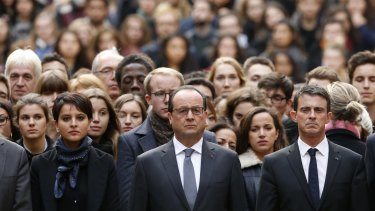 French President Francois Hollande, centre, flanked by French Prime Minister Manuel Valls, right, and French Education Minister Najat Vallaud-Belkacem, centre left, stands among students during a minute of silence in the courtyard of the Sorbonne University in Paris on Monday.