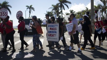 Demonstrators hold signs during a protest ahead of Donald Trump's arrival at Mar-a-Lago on Tuesday.